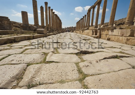 Roman road in Jerash, Jordan leading to the Oval Plaza, you can see ruts worn in the paving stones from the wheels of carts.