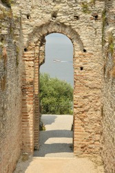 Roman stone archway in summer sun. amazing architecture built in Mediterranean with sea view through arch