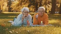 Romance at old age. Elderly couple blowing soap bubbles in the park in autumn. High quality photo