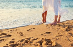 Romance concept. Honeymoon at the sea. Loving couple on the beach. Close up male and female feet on the sand.