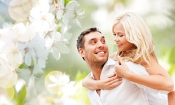 romance, people, love and dating concept - happy couple over cherry blossoms background
