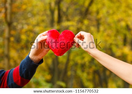 Romance relationship feelings symbolism concept. Two people holding heart. Humans presenting love symbol together. #1156770532