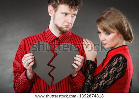 Romance relationship sadness unhappiness misfortune concept. Sad couple with broken heart. Girl with boy together holding black symbol of unhappy love. #1352874818