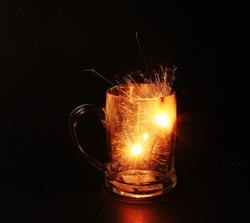 romance sparkler on beer glass on black background