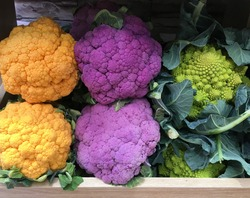 Romanesco broccoli and purple and orange cauliflower in a grocery. Variety of colorful vegetables in wooden boxes. Vegan health food concept