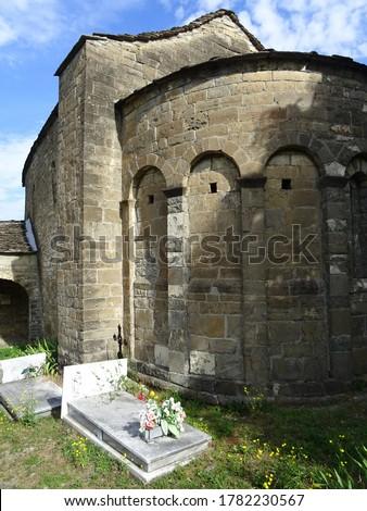Romanesque Church of Santa Eulalia  in the village of Oros Bajo. 11th century. View of the semicircular apse and the cemetery.  Serrablo Region. Aragon. Spain.                                stock photo