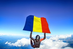 Romania flag. Flag in skydiving. People in free fall grab flag of Romania. Patriotism, men and flag.