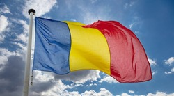 Romania flag, Romanian national symbol on a flagpole waving against blue cloudy sky