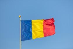 Romania flag waving against clean blue sky, close up. Romanian Flag on the mast