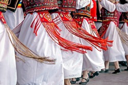 Romanian dancers in traditional costume, perform a folk dance.