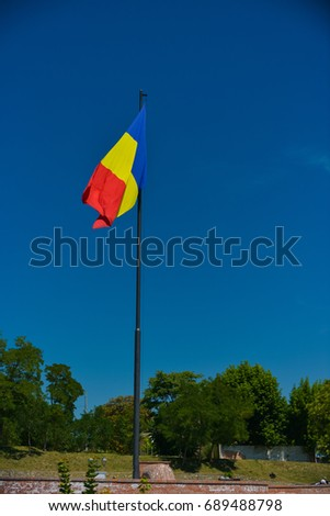 Romanian flag on a tall pole with deep blue sky in the background.  #689488798