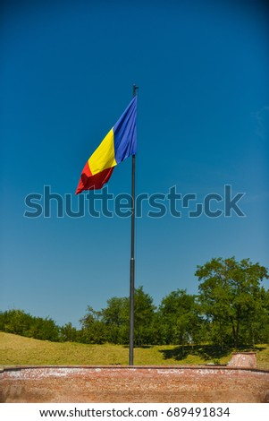 Romanian flag on a tall pole with deep blue sky in the background.  #689491834