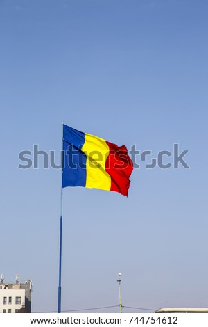 Romanian Flag on the mast. Romania flag of silk. Romanian flag on flagpole blowing in wind isolated against blue sky with copyspace.  #744754612