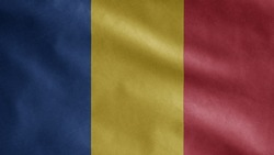 Romanian flag waving in the wind. Close up of Romania banner blowing, soft and smooth silk. Cloth fabric texture ensign background.