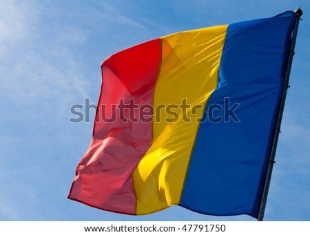 Romanian flag weaving against the blue sky