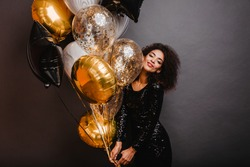 Romantic african girl holding bunch of party balloons. Indoor shot of graceful black lady celebrating birthday.
