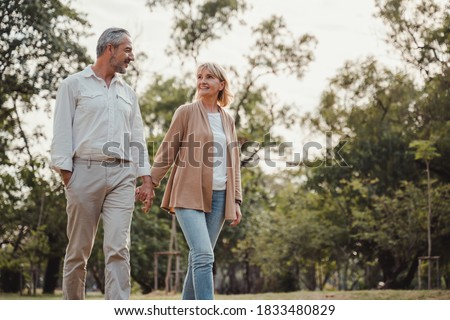 Romantic and elderly healthy lifestyle concept.Senior active caucasian couple holding hands looks happy in the park in the afternoon autumn sunlight,happy anniversary,happily retired with copy space.