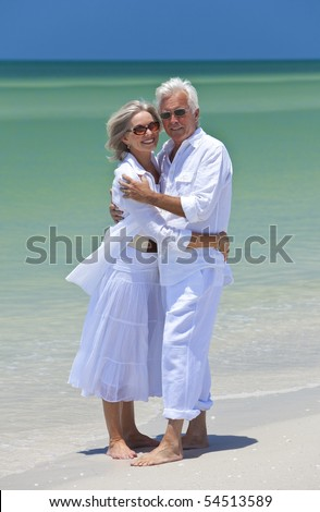 Romantic and happy senior man and woman couple dressed in white and embracing on a deserted tropical beach with bright clear blue sky