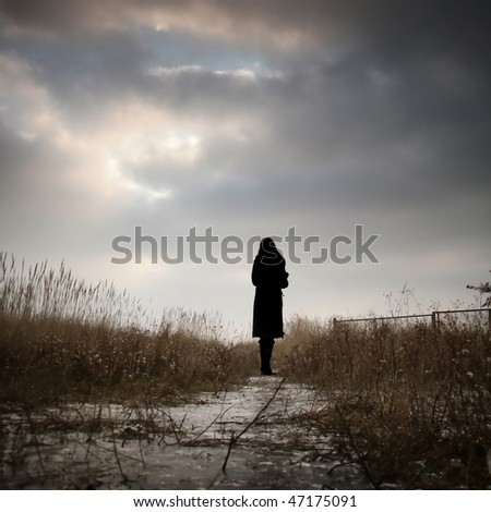 Romantic and nostalgic photograph of a girl silhouette staring at the winter sky