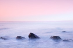 Romantic atmosphere in peaceful morning at sea. Big boulders sticking out from smooth wavy sea. Pink horizon with first hot sun rays.
