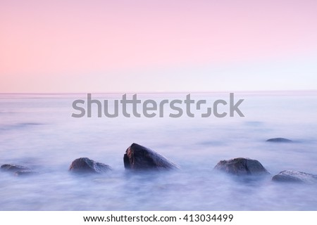 Stock Photo Romantic atmosphere in peaceful morning at sea. Big boulders sticking out from smooth wavy sea. Pink horizon with first hot sun rays.