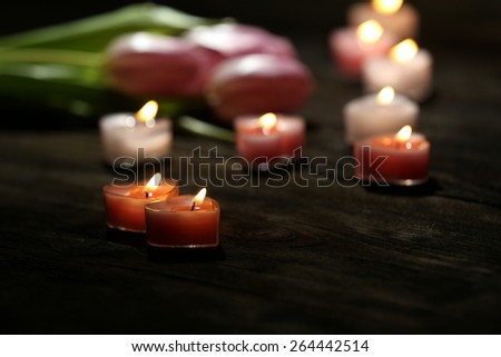Romantic atmosphere with candle lights and flowers on dark background
