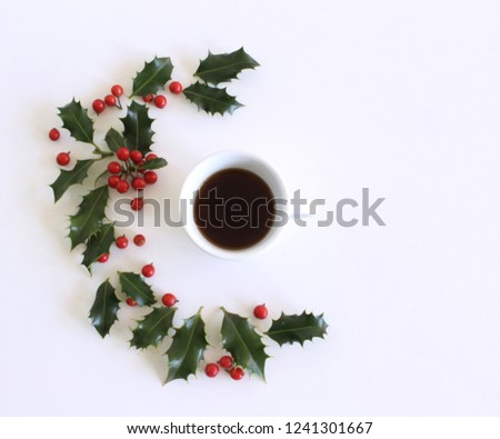 Romantic background with cup of coffee with holly  on  white table. Soft photo. Greeting card style. place for text. Top view flat lay with copy space for slogan or text.