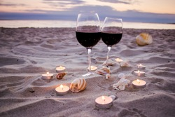 Romantic beach evening on the sunset: two glasses of wine, candles, shells, valentines day