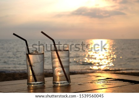 Romantic beach evening on the sunset with two glasses, two glasses and ice on table in beach with sunset, two glasses of water on the table with sea view. #1539560045