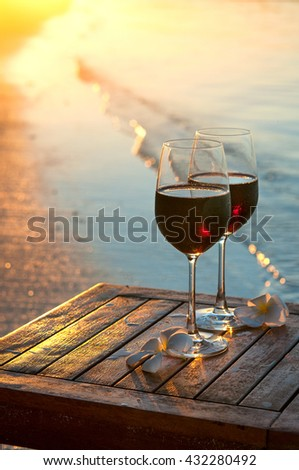 Romantic beach scene: two glasses of red wine at sunset near water line #432280492