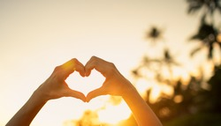 Romantic beach vacation holiday. Hand shaped hart on sunset sky.