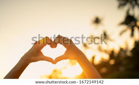 Romantic beach vacation holiday. Hand shaped hart on sunset sky.  Stockfoto ©