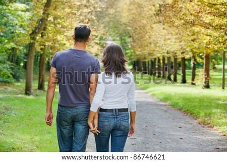 Romantic  Beautiful young couple walking in autumn park