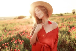 Romantic  blonde woman with flower in hand walking in amazing poppy field. Warm   sunset colors. Straw hat. Red dress. Soft colors.