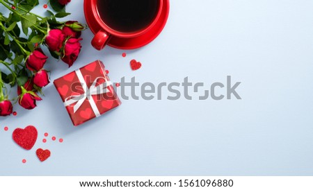 Romantic breakfast with red coffee cup, gift box, heart shaped, rose flowers on blue background. Happy Valentines Day card. Love and romance concept