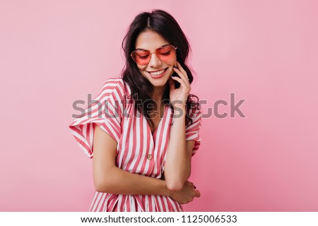 Romantic brown-haired girl in trendy heart glasses posing with shy smile. Indoor photo of graceful young woman in summer attire and accessories. #1125006533