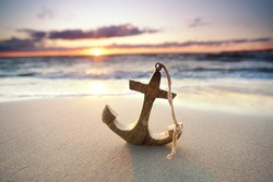 romantic colorful sunset at the sea with wooden anchor