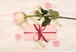 Romantic composition for Valentine's Day. A pink gift box and a delicate rose lie on a textile striped napkin and around pink candles in the shape of hearts on a white wooden background.Top view