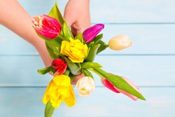 Romantic concept. Close up of colorful tulip flowers in female hands against light blue wooden background. Colorful and fresh flower bouquet. Mothersday concept.