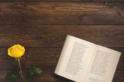 Romantic concept. Open book with poems and rose, on wooden background. Flat lay, top view, copy space.