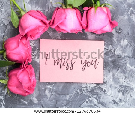 Romantic concept. Red roses and lettering I miss you on a gray concrete background #1296670534