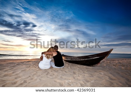 Romantic couple and boat on the beach at sunrise time