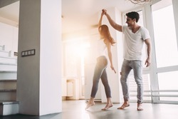 Romantic couple at home. Attractive young woman and handsome man are enjoying spending time together. Passionate couple is dancing on light modern kitchen with panoramic windows.