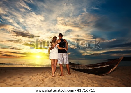 Romantic couple at uninhabited island at  sunrise time - stock photo