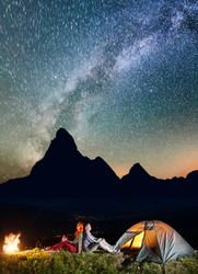 Romantic couple backpackers sitting by bonfire near tent under incredibly beautiful starry sky. Silhouette of the mountains and luminous village in the valley at night in background. Astrophotography