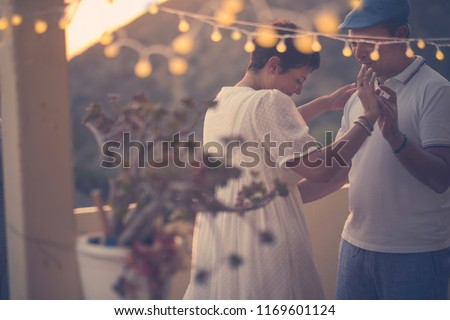 romantic couple dance together with love and romance during the down in the evening at home in the terrace. outdoor leisure activity for middle age woman and man. yellow light and nature in background