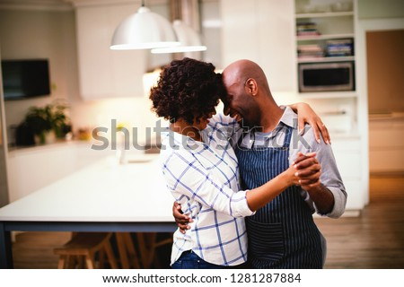 Romantic couple dancing in kitchen at home