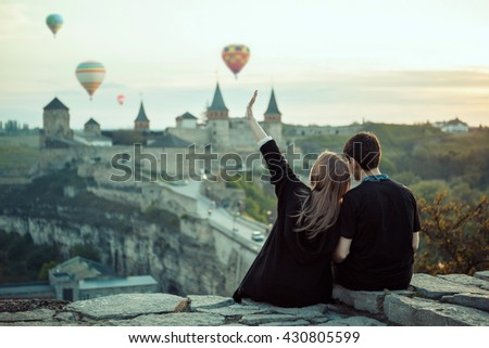 Romantic couple dating at the ancient castle. Watching balloons at sunset. Love story