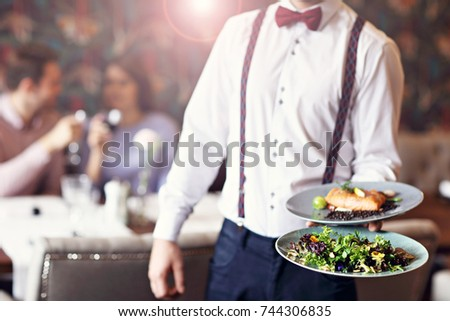 Romantic couple dating in restaurant being served by waiter #744306835