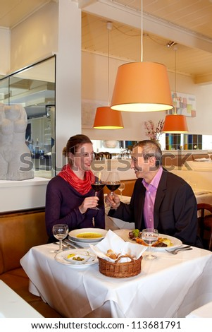 Romantic couple dining in a restaurant raising their wine glasses to each other in a toast